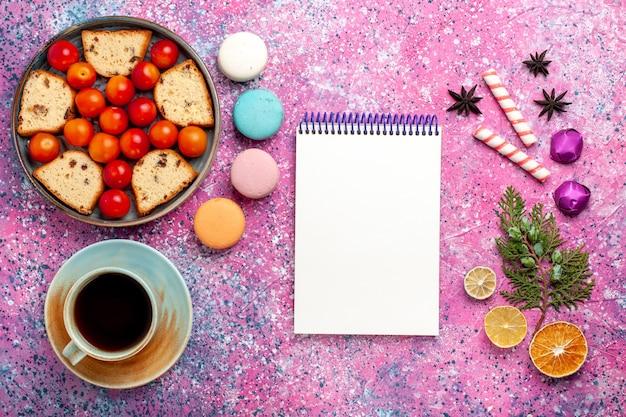 Vista superior deliciosa fatia de bolo com macarons de ameixas frescas e uma xícara de chá na superfície rosa claro