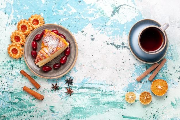 Vista superior deliciosa fatia de bolo com xícara de chá e biscoitos no bolo de parede azul assar torta de biscoito doce