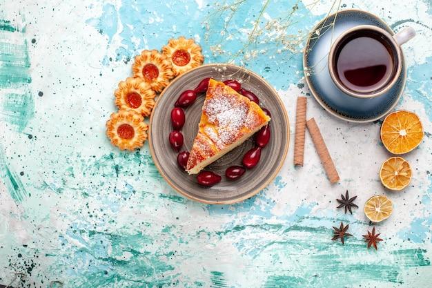 Vista superior deliciosa fatia de bolo com xícara de chá na superfície azul bolo assar torta biscoito doce