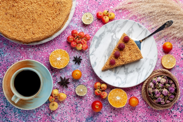 Vista superior deliciosa fatia de bolo redondo dentro do prato com uma xícara de chá na mesa rosa brilhante bolo torta de frutas biscoito doce assar