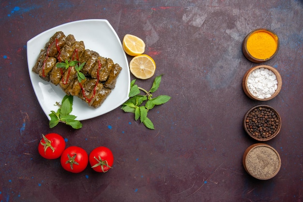 Vista superior deliciosa folha de dolma carne moída prato com limão e tomate na mesa escura prato folha jantar comida carne