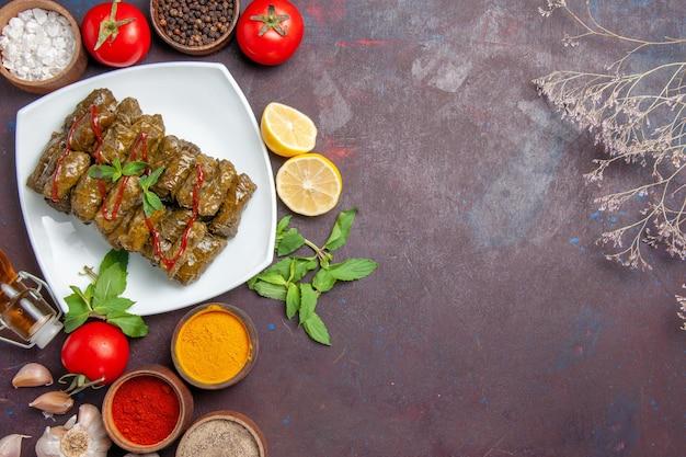Vista superior deliciosa folha de dolma com diferentes temperos e tomates em fundo escuro carne prato folha comida jantar