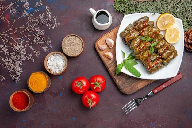 Vista superior deliciosa folha de dolma com rodelas de limão e temperos em fundo escuro prato folha carne jantar comida