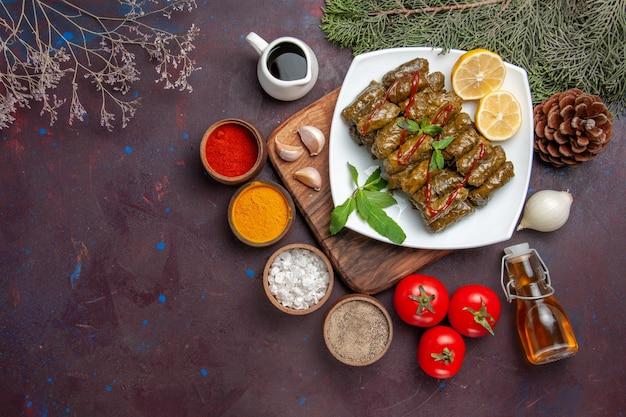 Vista superior deliciosa folha de dolma com rodelas de limão e temperos na mesa escura prato de carne prato de folha comida