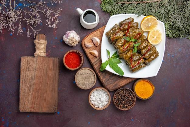 Vista superior deliciosa folha de dolma com rodelas de limão e temperos no fundo escuro prato de carne folha jantar refeição comida