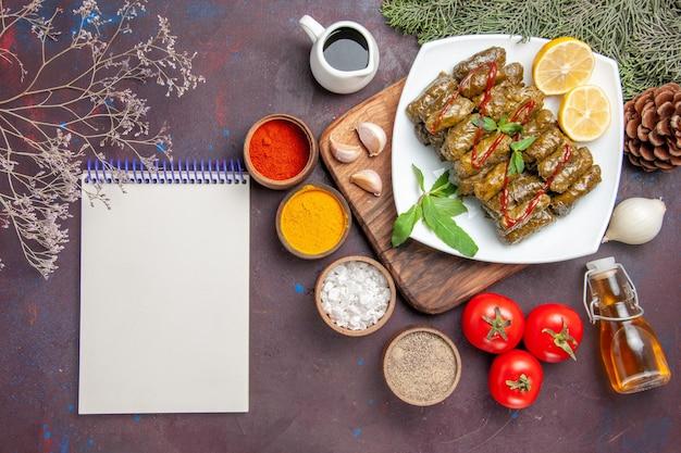 Vista superior deliciosa folha de dolma com rodelas de limão e temperos no fundo escuro refeição prato folha carne jantar comida