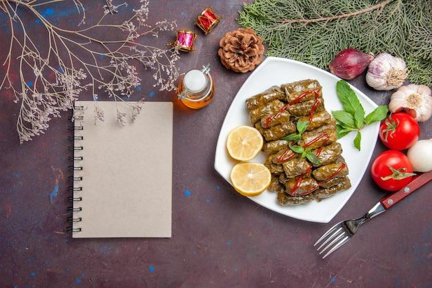 Vista superior deliciosa folha de dolma com rodelas de limão no fundo escuro carne prato folha jantar refeição comida