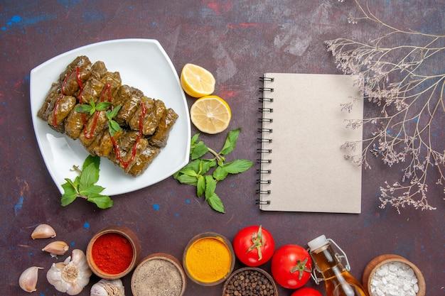 Vista superior deliciosa folha de dolma com temperos de limão e tomate na mesa escura prato folha comida carne jantar