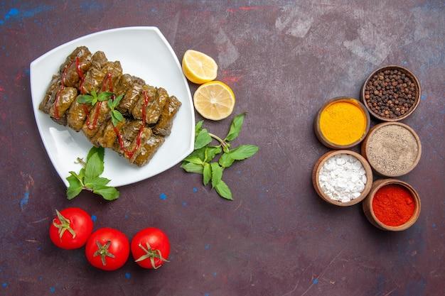 Vista superior deliciosa folha de dolma com temperos de limão e tomate na mesa escura prato folha jantar comida carne