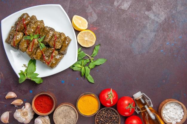 Vista superior deliciosa folha de dolma com temperos de limão e tomate no fundo escuro prato folha comida carne jantar