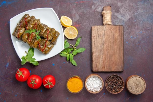 Vista superior deliciosa folha de dolma com temperos de limão e tomate no fundo escuro prato folha jantar comida carne