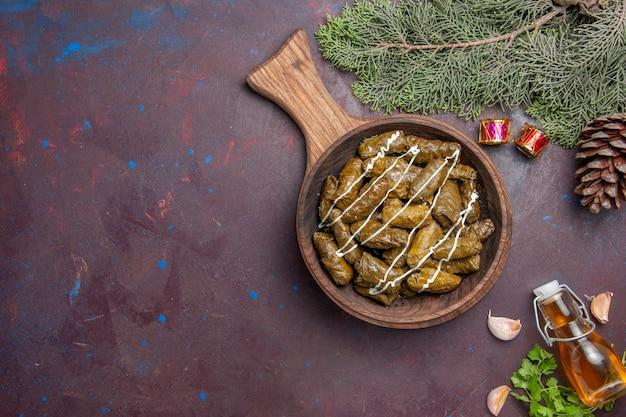 Vista superior deliciosa folha de prato de carne de dolma com diferentes temperos em mesa escura.