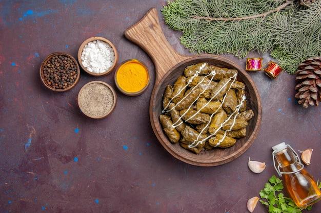 Vista superior deliciosa folha de prato de carne de dolma com temperos em fundo escuro carne jantar prato cor de calorias de comida