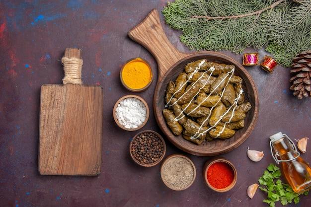 Vista superior deliciosa folha de prato de carne de dolma com temperos em fundo escuro carne jantar prato cor de calorias