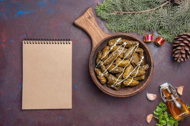 Vista superior deliciosa folha de prato de carne dolma com diferentes temperos em fundo escuro carne jantar prato cor de calorias de comida