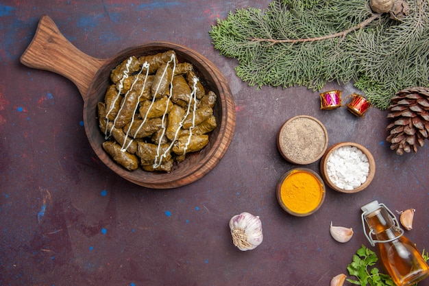 Vista superior deliciosa folha de prato de carne dolma com diferentes temperos no fundo escuro carne jantar prato cor de calorias