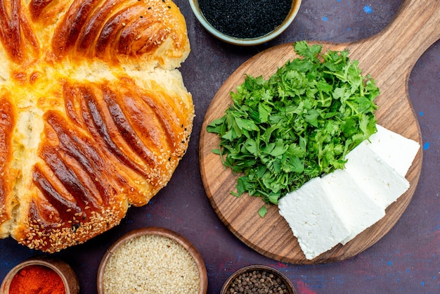 Vista superior deliciosa massa com verduras e queijo branco em fundo escuro.