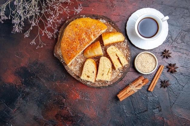 Vista superior deliciosa massa doce com uma xícara de chá na mesa escura