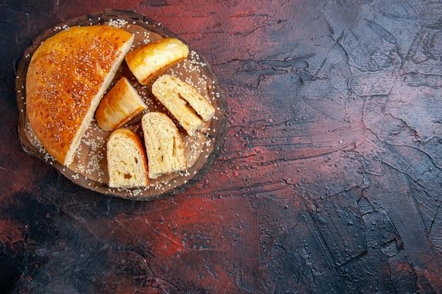 Vista superior deliciosa massa doce fatiada em pedaços na superfície escura