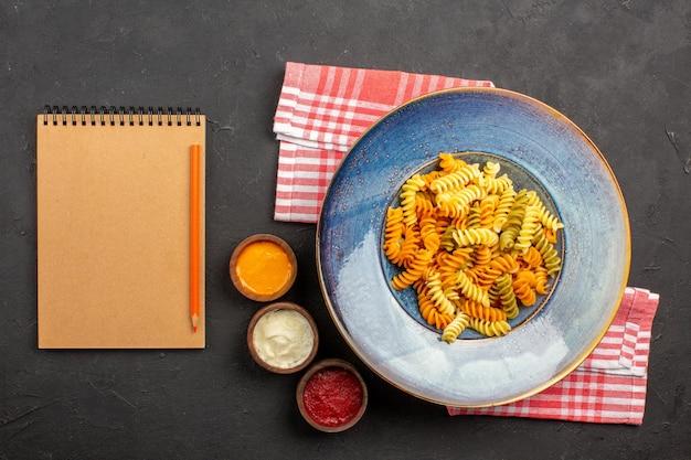 Vista superior deliciosa massa italiana incomum massa espiral cozida no fundo escuro prato de massa refeição cozinhando o jantar