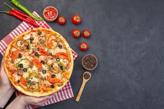 Vista superior deliciosa pizza de queijo com azeitonas, pimenta e tomate em superfície escura