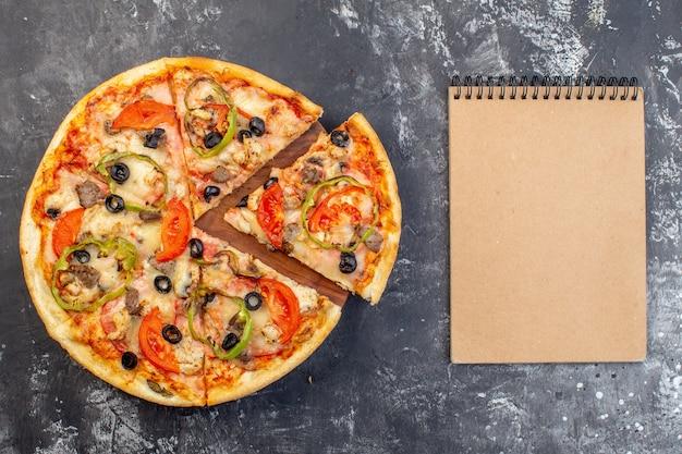 Vista superior deliciosa pizza de queijo fatiada e servida em superfície cinza