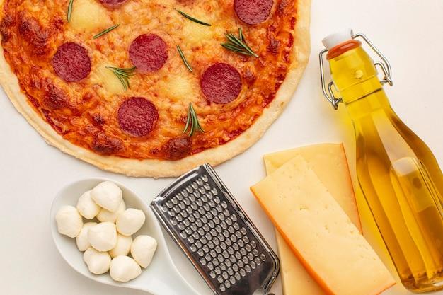 Vista superior deliciosa pizza e garrafa de óleo