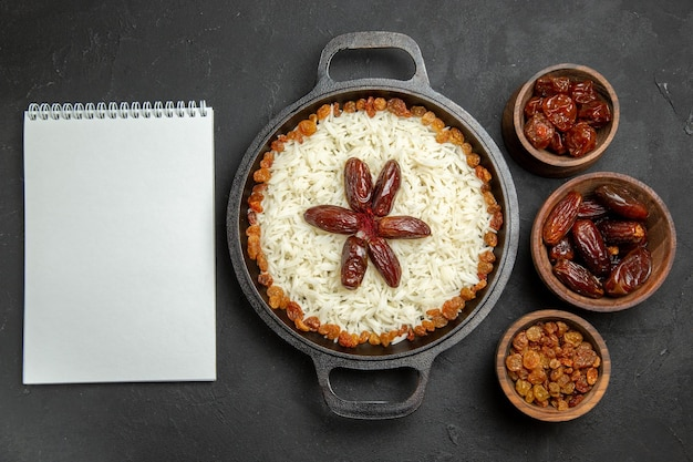 Vista superior deliciosa refeição de arroz cozido plov com passas dentro da panela na mesa escura