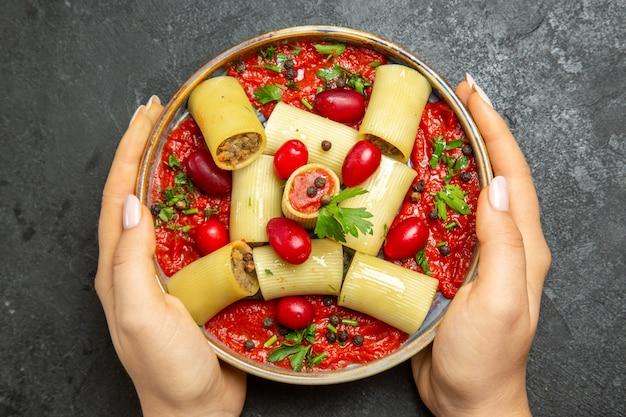 Vista superior deliciosa refeição de massa italiana cozida com carne e molho de tomate na superfície cinza.