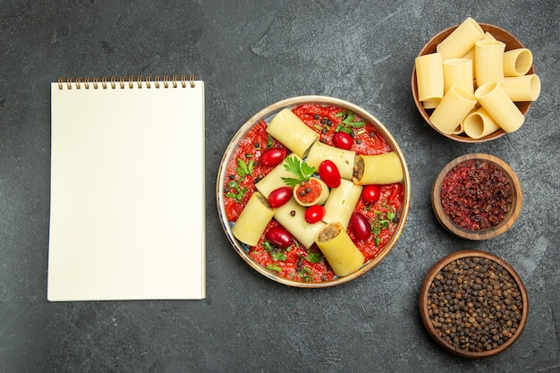 Vista superior deliciosa refeição de massa italiana cozida com molho de tomate e temperos no fundo cinza.