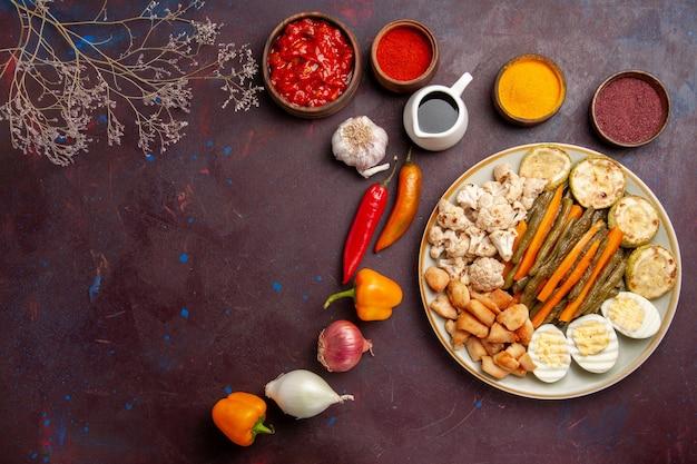 Vista superior deliciosa refeição de ovo com vegetais cozidos e temperos em espaço escuro