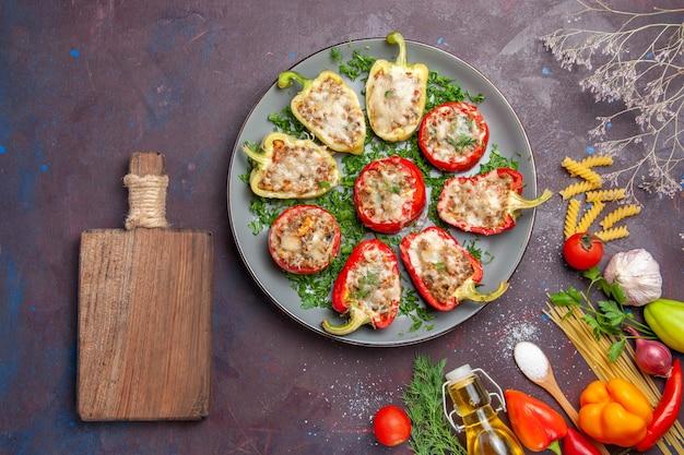 Vista superior deliciosa refeição de pimentões assados com carne dentro e verduras em fundo escuro.