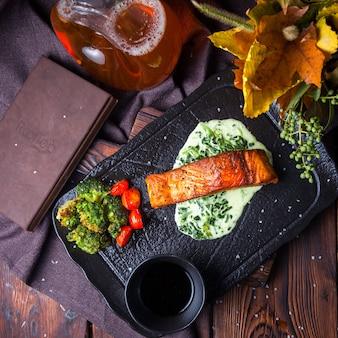 Vista superior deliciosa refeição na bandeja preta sobre fundo escuro de madeira com decorações