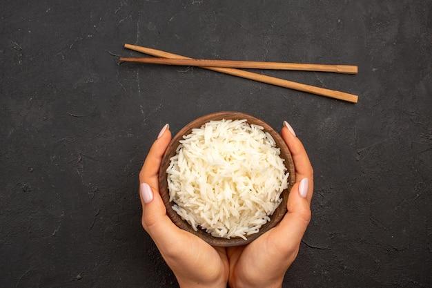 Vista superior deliciosa refeição saborosa simples de arroz cozido dentro de um prato no espaço escuro