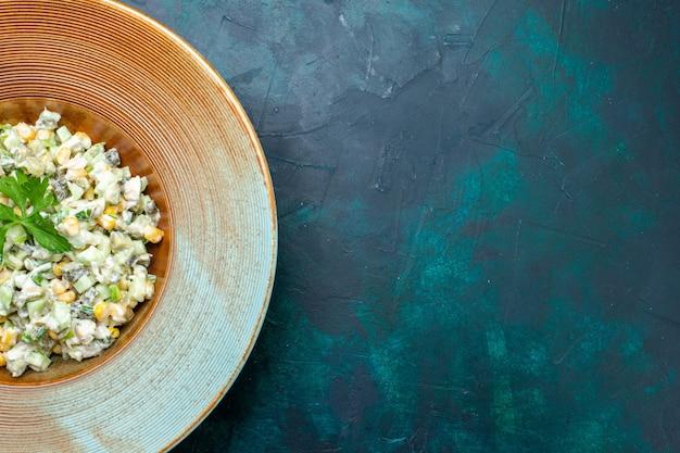 Vista superior deliciosa salada com vegetais fatiados dentro do prato na mesa azul escura.