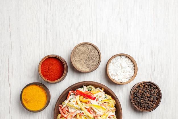 Vista superior deliciosa salada de frango com diferentes temperos na mesa branca lanche refeição madura cor carne salada fresca