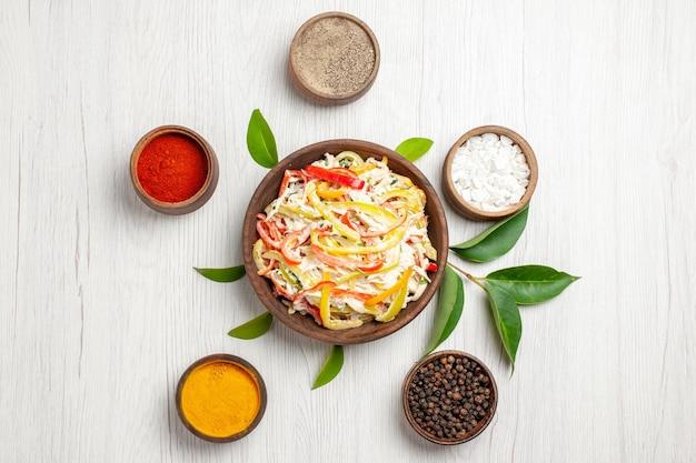 Vista superior deliciosa salada de frango com diferentes temperos na mesa branca, lanche refeição madura salada fresca de carne