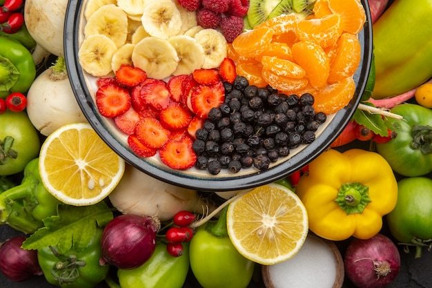 Vista superior deliciosa salada de frutas dentro do prato com frutas frescas na foto de dieta exótica de árvore de frutas tropicais cinza