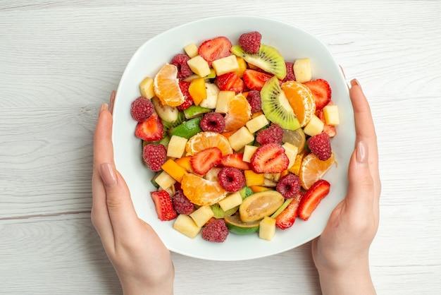 Vista superior deliciosa salada de frutas em fatias de frutas dentro do prato na cor branca vida saudável foto frutas maduras maduras