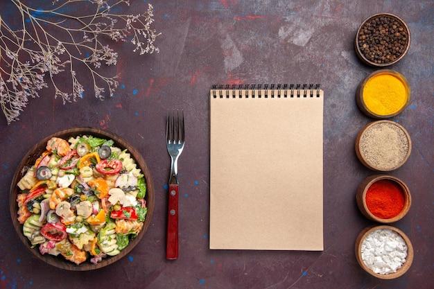 Vista superior deliciosa salada de vegetais com diferentes temperos na mesa escura, dieta saudável, salada de vegetais, almoço