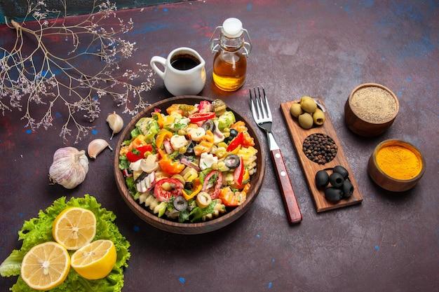 Vista superior deliciosa salada de vegetais com rodelas de limão e salada verde em fundo escuro