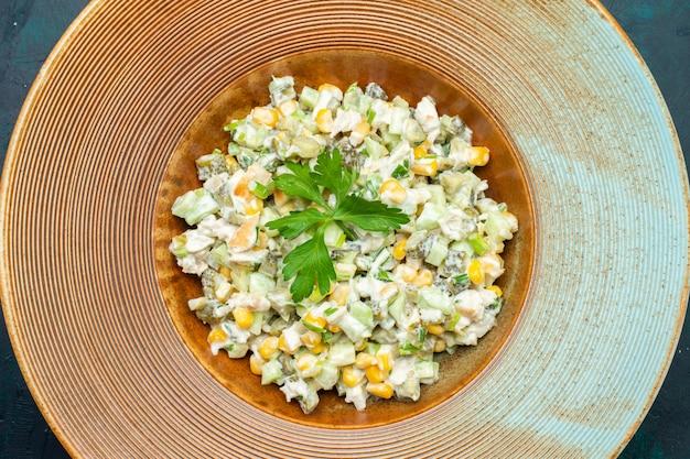 Vista superior deliciosa salada de vegetais dentro do prato na mesa azul escura.