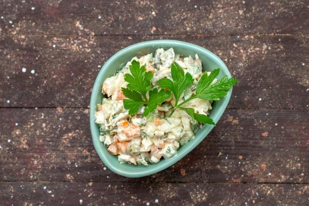Vista superior deliciosa salada mayyonaise dentro de prato verde com verde no marrom woode salada mesa comida refeição lanche foto