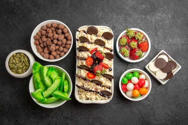 Vista superior deliciosa sobremesa com biscoitos de frutas e doces em fundo escuro.