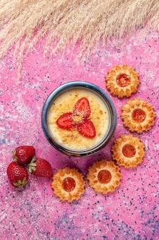 Vista superior deliciosa sobremesa cremosa com bolinhos na superfície rosa claro sobremesa sorvete de frutas vermelhas