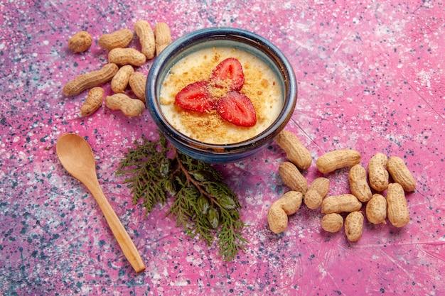 Vista superior deliciosa sobremesa cremosa com fatias vermelhas de morangos e amendoins no fundo rosa claro sobremesa sorvete cor doce frutas frutas vermelhas