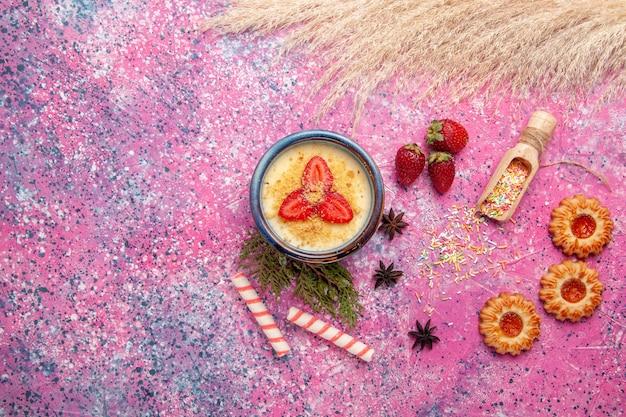 Vista superior deliciosa sobremesa cremosa com morangos fatiados vermelhos e biscoitos em um fundo rosa claro sobremesa sorvete de frutas doces