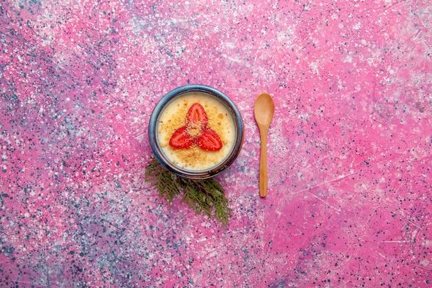 Vista superior deliciosa sobremesa cremosa com morangos fatiados vermelhos em fundo rosa claro sobremesa sorvete de frutas doces baga