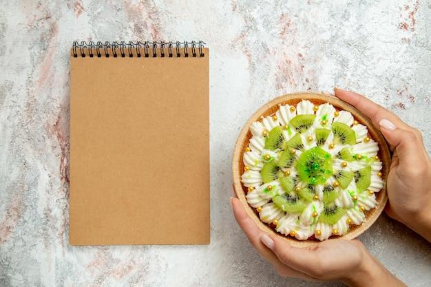 Vista superior deliciosa sobremesa de kiwi com creme branco e kiwis fatiados no fundo branco.