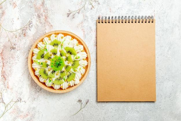 Vista superior deliciosa sobremesa de kiwi com creme branco saboroso e frutas fatiadas no fundo branco.